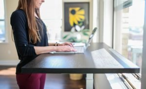 Woman Standing at a Tall Desk